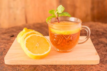 Lemon Teacup with lemon slices and mint leaf on a wooden background. Beverage concept, Close-up, Selective Focus