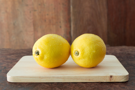 Lemons on a wooden plate - Close up fresh of lemons on a wooden plate background with copy space, Selective focus. Stock Photo - 98513248
