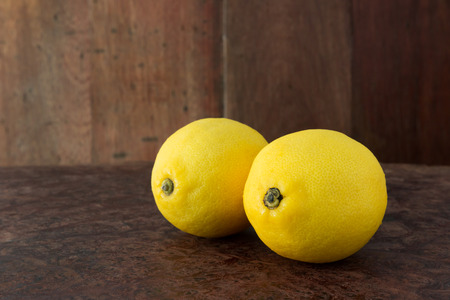 Lemons on a wooden plate - Close up fresh of lemons on a wooden plate background with copy space, Selective focus. Stock Photo - 98378505