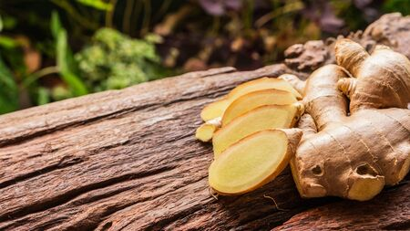 Ginger root - Fresh ginger root and sliced on old plank with nature background. Close-up, Selective focus