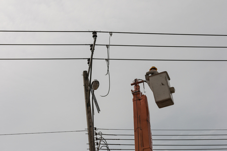 Electrician working on electric pole at an altitude to installs cable high voltage against to transformer with cloudy sky. Stock Photo - 98513279