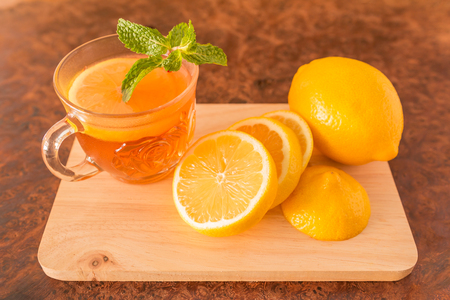 Lemon Teacup with lemon slices and mint leaf on a wooden background. Beverage concept, Close-up, Selective Focus Stock Photo - 98439455