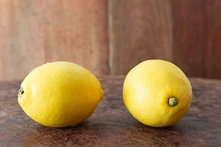 Lemons on a wooden plate - Close up fresh of lemons on a wooden plate background with copy space, Selective focus. Stock Photo