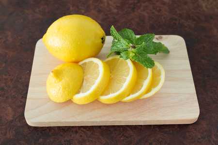 Lemons on a wooden plate - Close up sliced of fresh lemons on a wooden plate background, Selective focus.