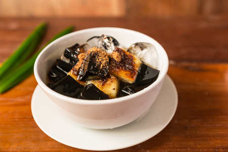 Grass jelly dessert herbal gelatin or jelly black with pineapple, syrup, ice, and brown sugar on the wooden background. Chinese style.