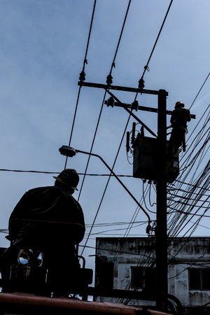 Bangkok, Thailand - August 5, 2017: Electrician working on electric pole at an altitude to installs cable high voltage against to transformer with cloudy sky.