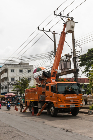 Bangkok, Thailand - August 5, 2017: Electrician working on electric pole at an altitude to installs cable high voltage against with cloudy sky.  Editorial