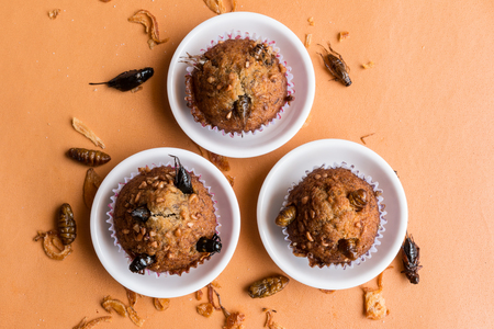 Banana cupcakes with insect foods - Three banana cupcakes with insect foods on the small white bowl and crispy shallots fried on orange tablecloth background. Healthy meal high protein diet concept. Top view, Selective focus.