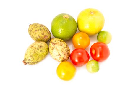 Organic green fruit - Lemon, tomato, Hog Plum or Spondias Pinnata fruits isolated on a white background. The Papaya Salad is Thai food recipes with Organic green fruits add toppings. Stock Photo