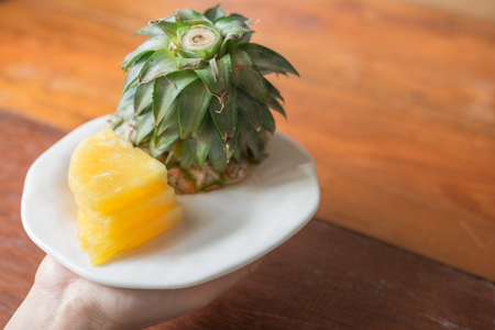 Pineapple with slices - Human female hands holding pineapple slices. Tropical fruit concept. Close-up, Selective focus. Stock Photo