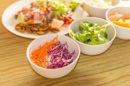 Fresh vegetable salad with worm insects - Vegetable salad with worm insects in the kitchen on a wooden table. Healthy meal high protein diet concept.