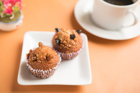 Insect food in a banana cupcake with black coffee in a white cup. Healthy meal high protein diet concept. Close-up, Selective focus.