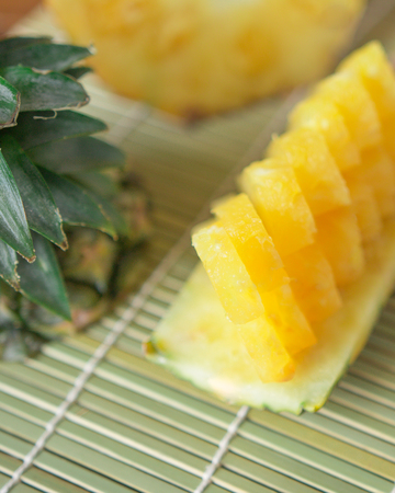 Pineapple with slices - Fresh of pineapple slices Asian-style on the bamboo place mats background. Tropical fruit concept. Selective focus. Stock Photo