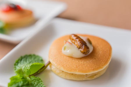 Insect pancake - Worm insect with Mayonnaise on the pancakes and mint leaf for breakfast. Close-up, Selective focus.