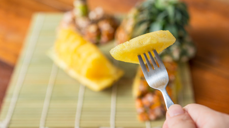 Pineapple with slices - Human female hands holding pineapple slices on a silverware. Tropical fruit concept. Close-up, Selective focus.