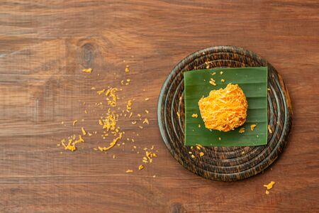 Foi Thong,  (Shredded Egg Yolk Tart) Thai desserts ingredients, used Egg yolks and sugar are boiled in sweet syrup and then formed into hairlike shapes on a wooden plate. Thai traditional desserts, Top view.