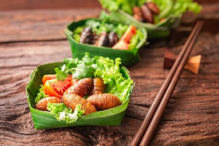 Fried Worm, Insect food with vegetables, tomato in the bowls made from banana leaves on wooden background. Closeup, Selective focus.