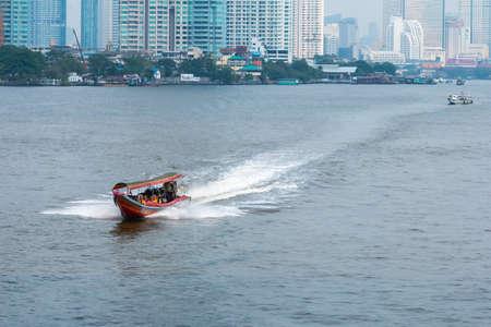 Bangkok, Thailand - January 16, 2020: Long-tail boat with tourists exploring Chao Phraya River in Bangkok, Thailand.on January 16, 2020.