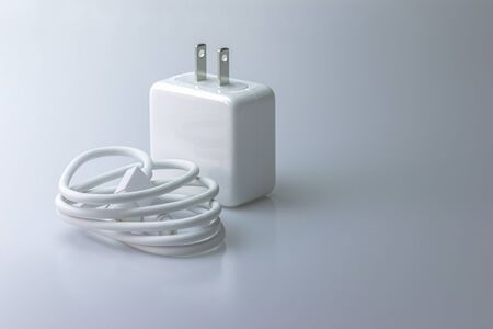 White electric charging with USB cable for phone on gray background