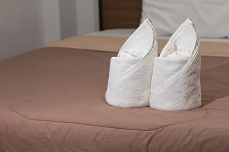 White towels set on the bed in the hotel room.