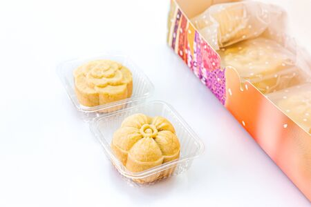 Two piece of delicious pineapple bread near the colorful box on a white background. Copy space, Selective focus.