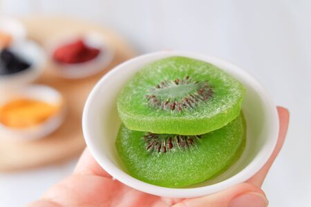 Woman hand holding dried fruit kiwi slices in white bowls. Organic healsy healthy snack. Selective focus. Stock Photo
