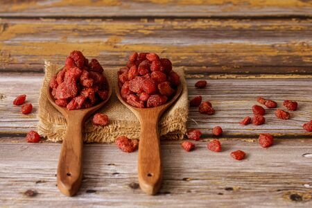 Dried strawberries in a wooden ladles with an old wooden background. Stock Photo