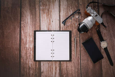 Overhead view of Traveler's accessories on wooden table background with Photo camera, Smart phone, Glasses and Note book with copy space. traveling concept background. Flat lay.