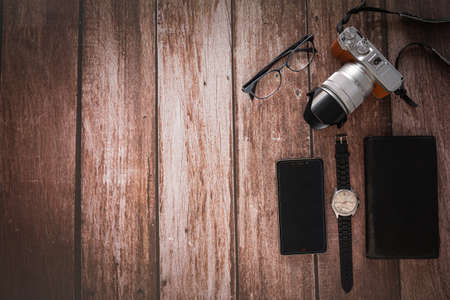 Overhead view of Traveler's accessories on wooden table background with Photo camera, Smart phone, Glasses with copy space. traveling concept background. Flat lay.