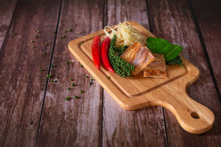 Spices with ingredients, Stir-Fried Spicy and herb with dried fish fillet on a cutting board with wooden dark background. Thai food concept. Stock Photo