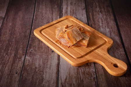 Dried fish fillet on a cutting board with a wooden dark background. Thai food concept.