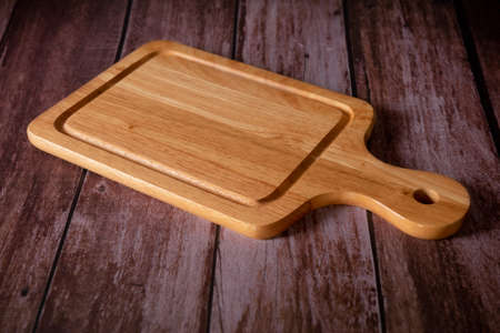 Cutting board with wooden dark background. Food cooking concept.