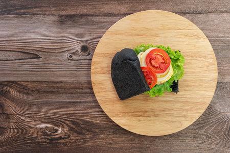 Black bread sandwich on a wooden kitchen board background. Top view.