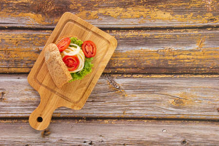 Sandwich bread with melting Cheese, Ham, Tomato, Salad, Onion on a wooden chopping board with copy space. Top View.