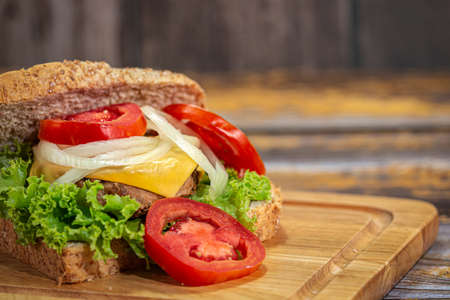 Close-up Sandwich bread with Cheese, Ham, Tomato, Salad, Onion on a wooden chopping board with copy space. Stock Photo