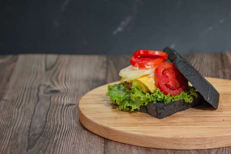 Delicious breakfast charcoal sandwiches on wooden cutting boards with copy space. Stock Photo