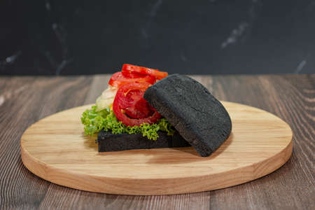 Sandwich bread made of charcoal with melting Cheese, Ham, Tomato, Salad, Onion on a wooden chopping board over dark background