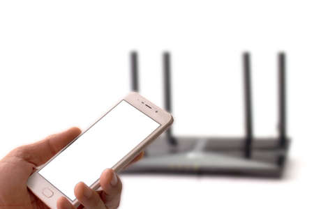 Man holding smartphone with wireless internet router background, closeup of hand.