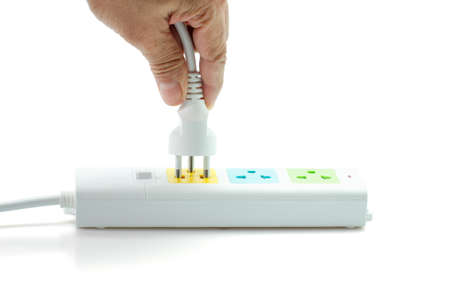 Close-up, Hand holding an electric plug ready to connect power strip on white background. Stock Photo
