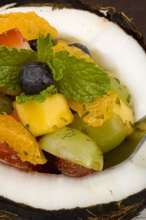 minty: Tropical, minty, fruit salad served in a coconut shell with honey yogurt on the side. Stock Photo
