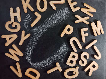 English alphabet letter C displaying with all alphabetic text collection on black board surface hand written and wooden mixed background.