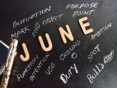 June word presented with multiple business related terminology on black board at educational concept.