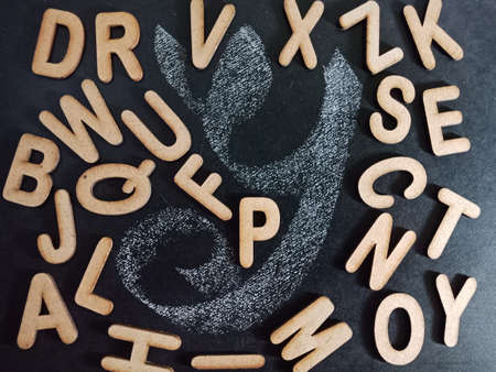 English alphabet letter displaying with all alphabetic text collection on black board surface hand written and wooden mixed background.