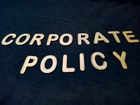 Corporate policy word presented on black board with wooden text art texture at educational style.