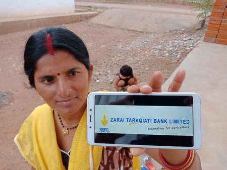 DISTRICT KATNI, INDIA - JUNE 02, 2020: An indian woman holding smart phone with displaying Zarai Taraqiati bank islamabad logo on screen, modern banking education concept for village people.