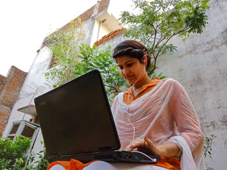DISTRICT KATNI, INDIA - MAY 16, 2020: An indian corporate girl working on laptop, work from home at garden.