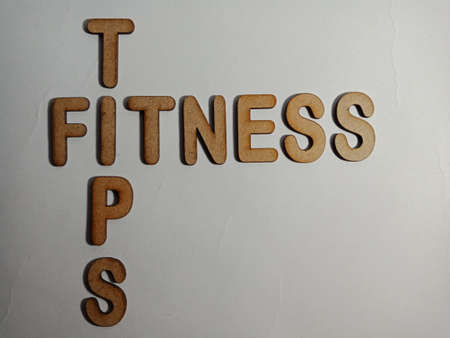 Fitness Tips word display with cross wooden alphabet concept for informational awareness.