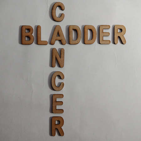 Bladder cancer word display with cross wooden alphabet concept for informational awareness.