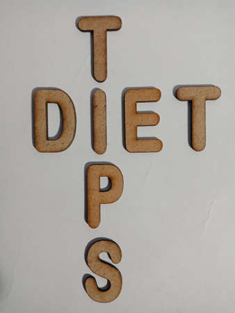 Diet Tips word display with cross wooden alphabet concept for informational awareness.