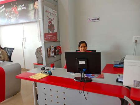 DISTRICT KATNI, INDIA - JANUARY 29, 2020: An Asian female staff working on desktop at Hero automobile motorcycle agency in Indian Territory.